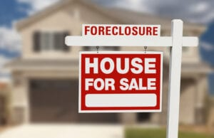 Foreclosure,House,For,Sale,Sign,In,Front,Of,Beautiful,Home.